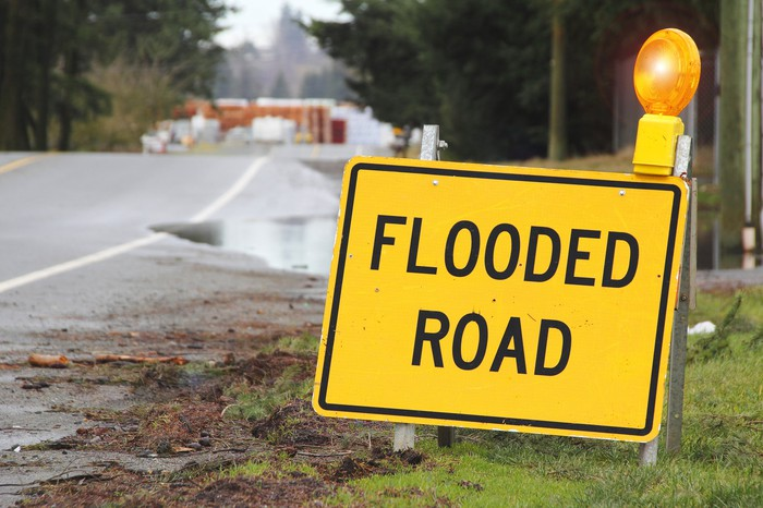"Yellow ""Flooded Road"" sign along side of road."