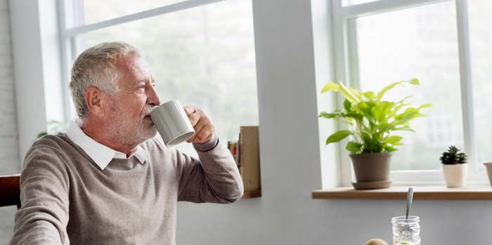 An old man drinking out of a coffee mug staring out a window.