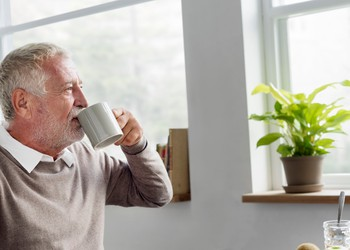 senior man drinking coffee looking out window