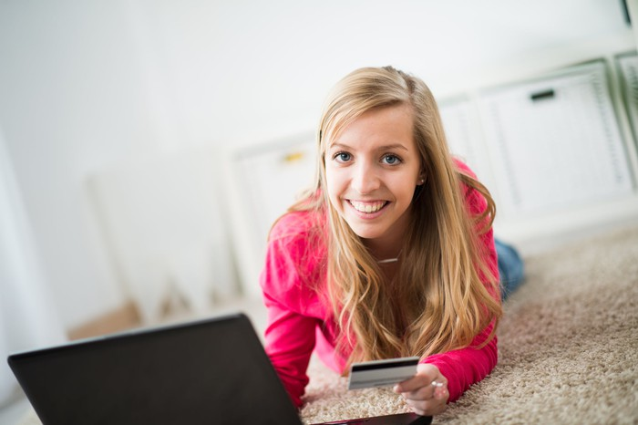 Teenage girl holding credit card while on a computer.