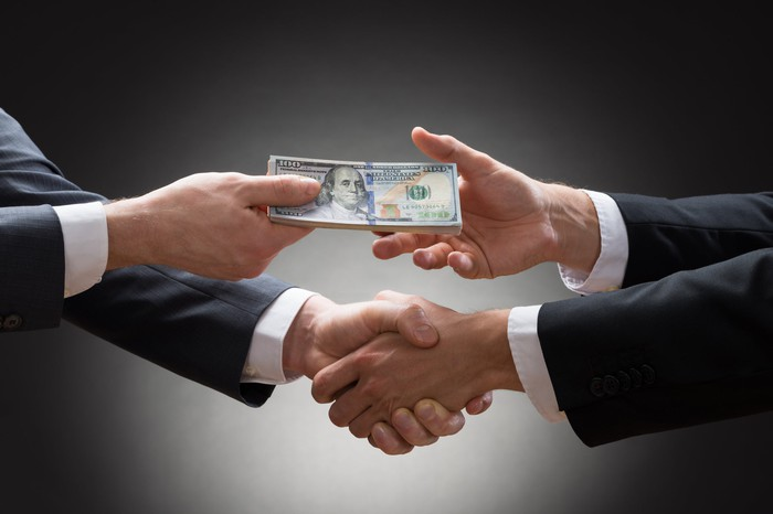 Two people in business attire shake hands while exchanging money.