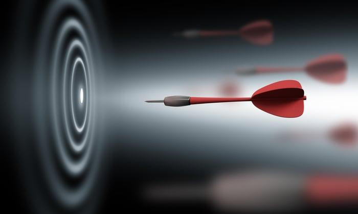 A red dart shooting toward a black and white bullseye