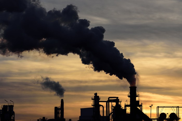Black smoke billowing out of a factory smokestack silhouetted against a sky at sunset
