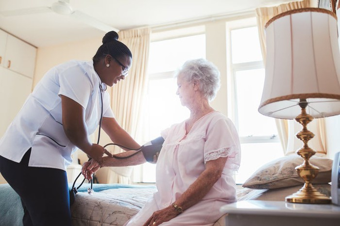 Nurse takes an elderly patient's blood pressure in a skilled nursing facility.