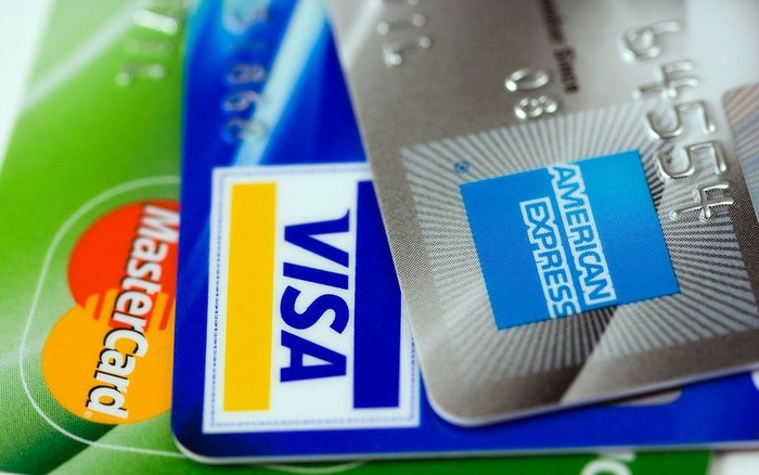 Three credit cards shown fanned out: one American Express card, one Visa card, one Mastercard card.