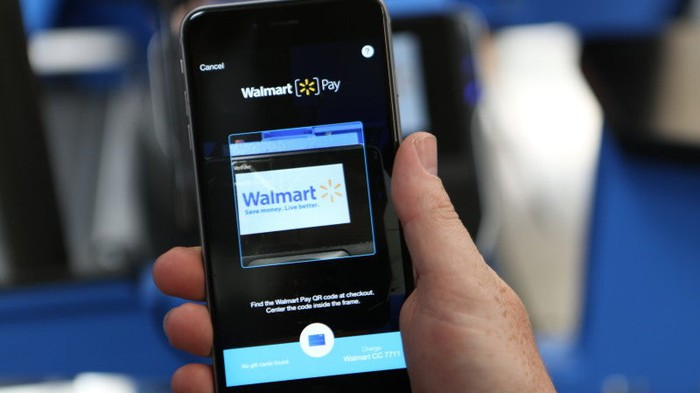 A hand holding a smartphone displaying the Walmart Pay app.