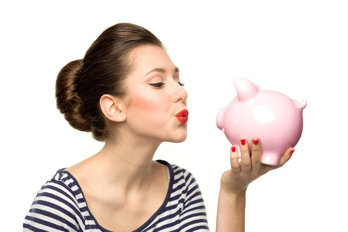 A woman puckers her lips at a piggy bank in her hand.