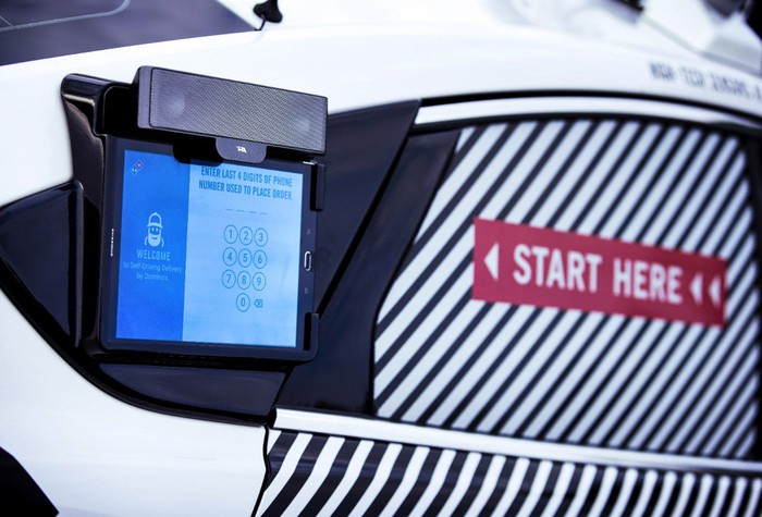 A close-up of a touchscreen on the side of the self-driving Ford Fusion Hybrid pizza-delivery test vehicle.