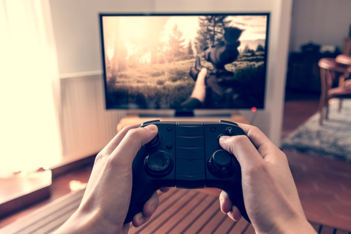 Man's hands holding a video game controller with a large TV screen displaying a game in the background.