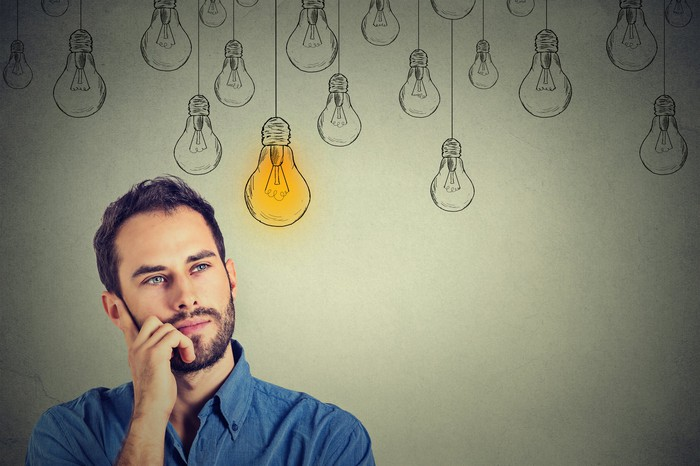 Man with hand to his face in front of drawings of multiple light bulbs with one colored brightly