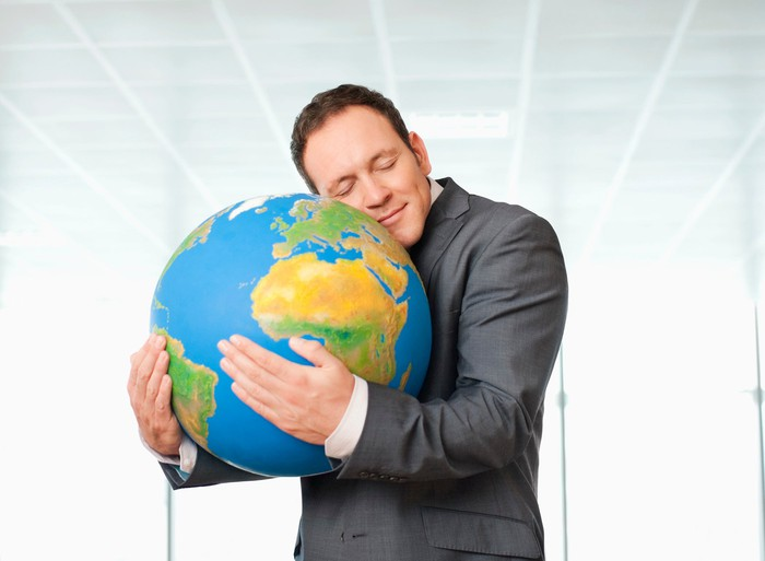 Man in suit embracing a globe.