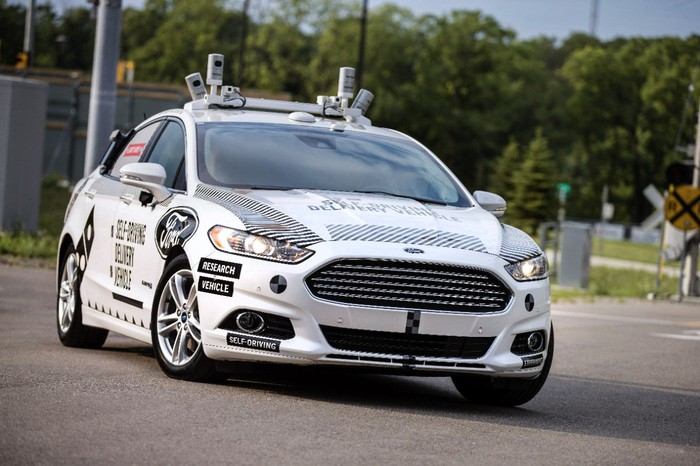 A white Ford Fusion Hybrid with self-driving sensors and logos indicating that it's a self-driving Domino's Pizza delivery vehicle.