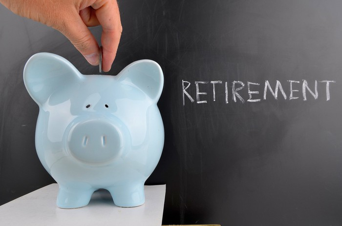 Man putting coin in a piggy bank with the word retirement written on a chalk board in the background.