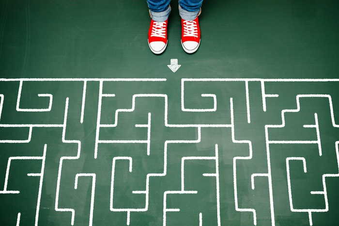 Someone with bright red shoes standing at the beginning of a complex maze.