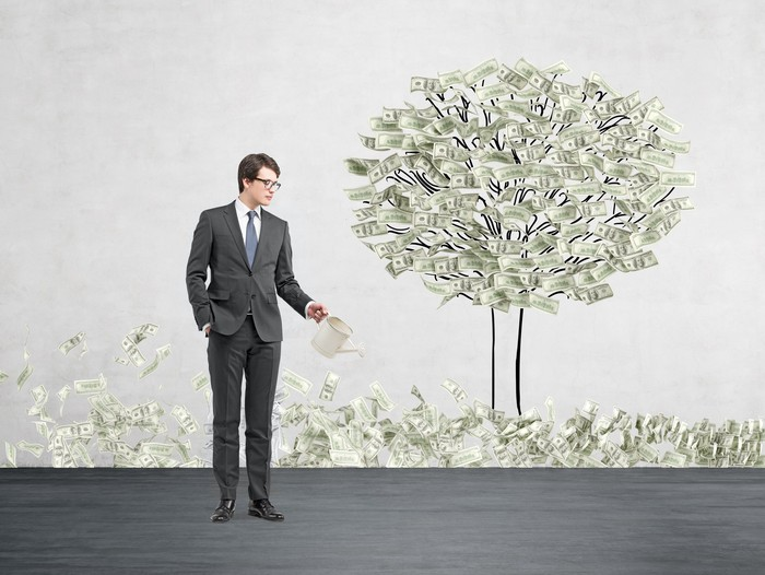 "A man wearing a suit waters a ""tree"" that has money for leaves."