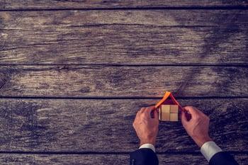 Pair of Hands Building Wooden Block Home
