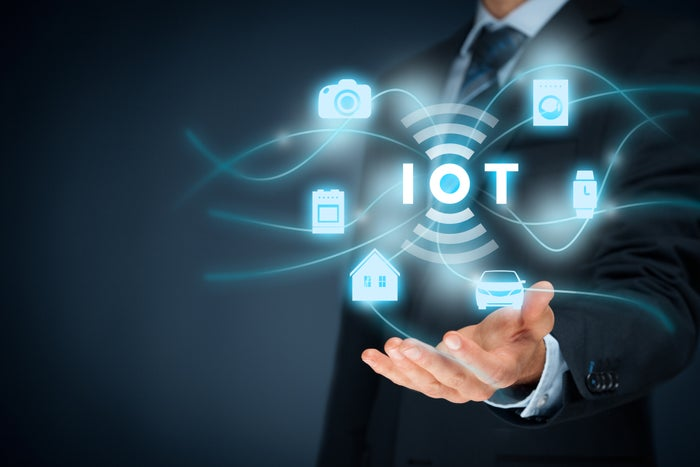 Businessman holds out one hand under an IoT graphic surrounded by connected device icons such as a car, a house, and a smartwatch.