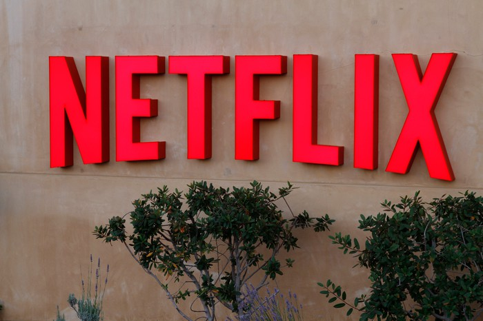 Red Netflix logo on a grey stone wall outside the company's headquarters in Los Gatos, Calif.