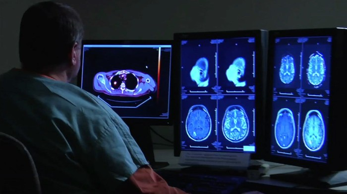 Man in scrubs sitting in front of monitors showing medical images