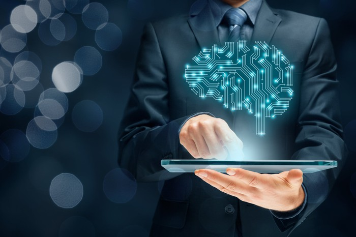 Man holding tablet with image of circuits in shape of brain projected above the tablet