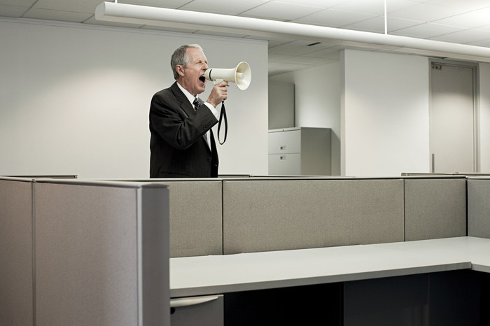 man in suit shouting through a foghorn in an empty office.