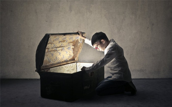 A boy opening a treasure chest.