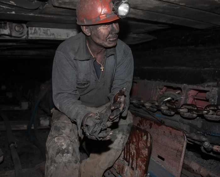 A coal miner standing, dirty, in a mine.