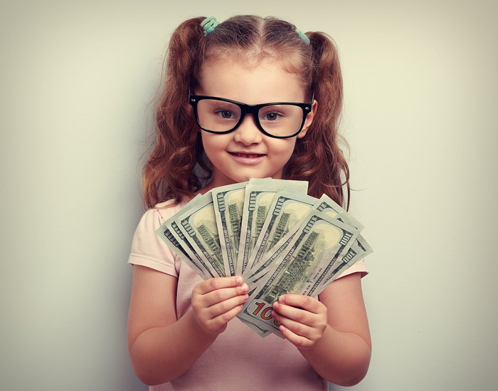A bespectacled girl in ponytails fanning $100 bills with both hands