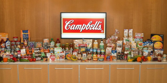 The Campbell's logo on a screen, with all of the company's products laid out on a countertop.