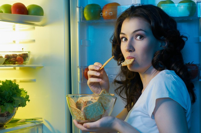 Woman holding a bowl of crackers, one in her mouth, standing at a refrigerator looking surprised like someone who has been caught red-handed.
