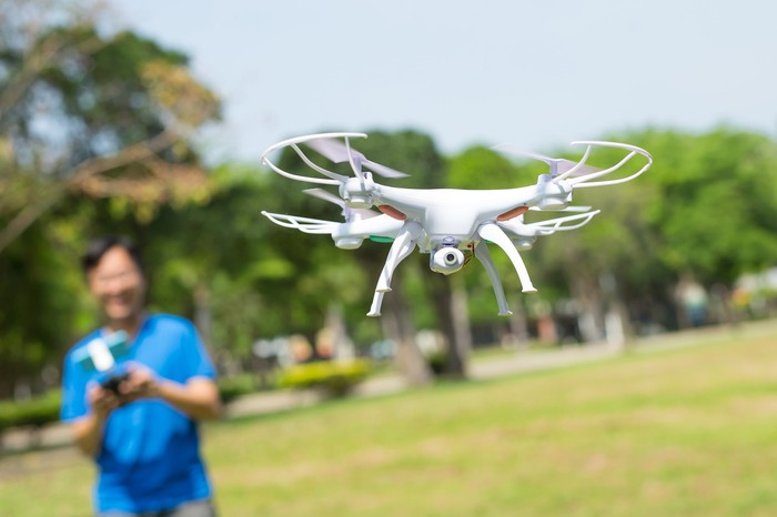 Man playing with quadcopter drone in a park