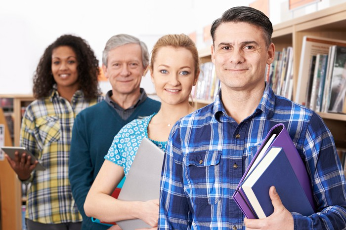 Two older men and two older women, standing in a line and surrounded by bookshelves, clutch a variety of books and electronic devices.