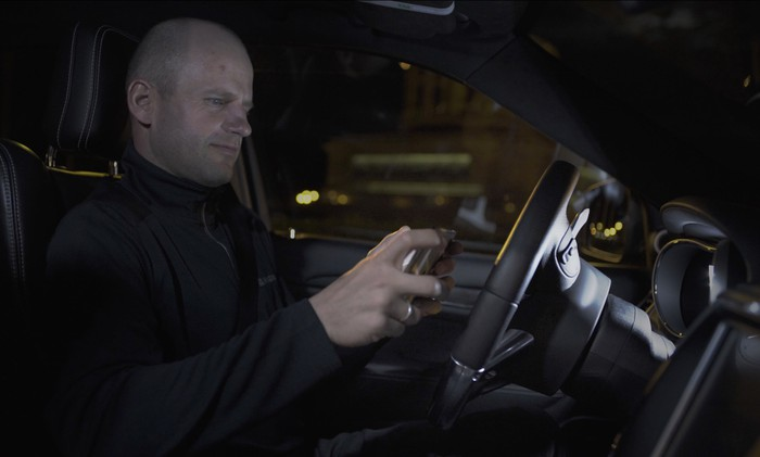 A side-profile view of a male driver in a car's interior. The driver isn't touching the steering wheel, but there are no obvious signs of self-driving hardware.