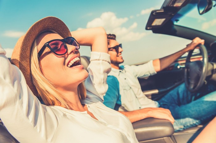 Man and woman driving in convertible