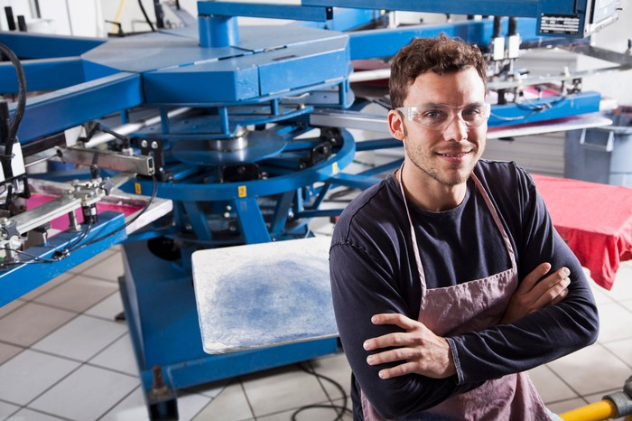 A manufacturing worker with his arms crossed standing in front of machinery.