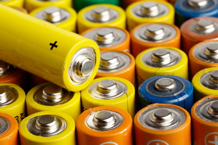 A AA battery sits atop other AA batteries.