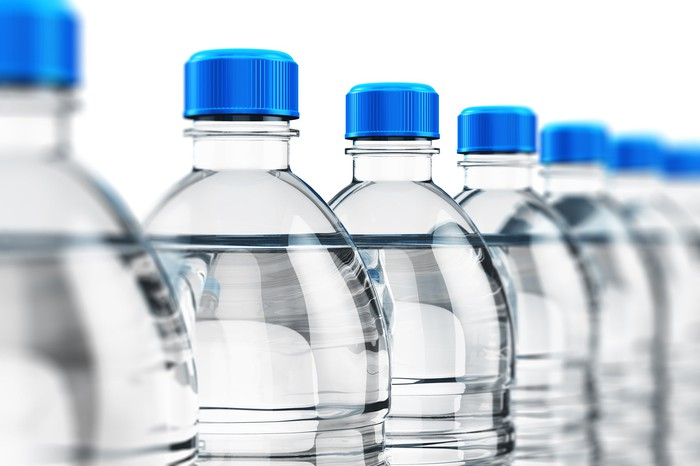 A line of water bottles with blue tops.