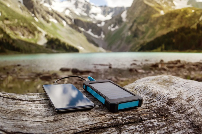 A phone sits next to a solar charger overlooking a mountain.
