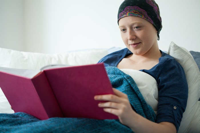 A female cancer patient in bed reading a book and smiling