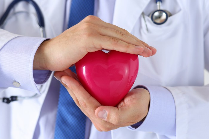 A doctor holding a red toy heart between his hands