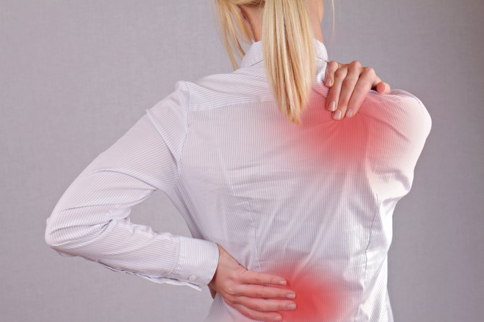 A woman rubbing her upper and lower back in pain