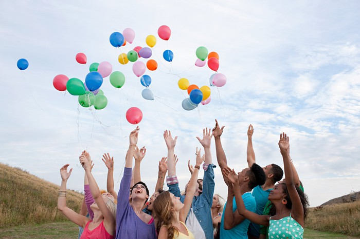 Group of people releasing balloons into the air
