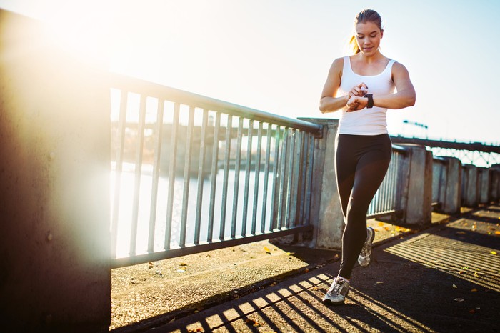 A woman checks her fitness tracker while jogging.
