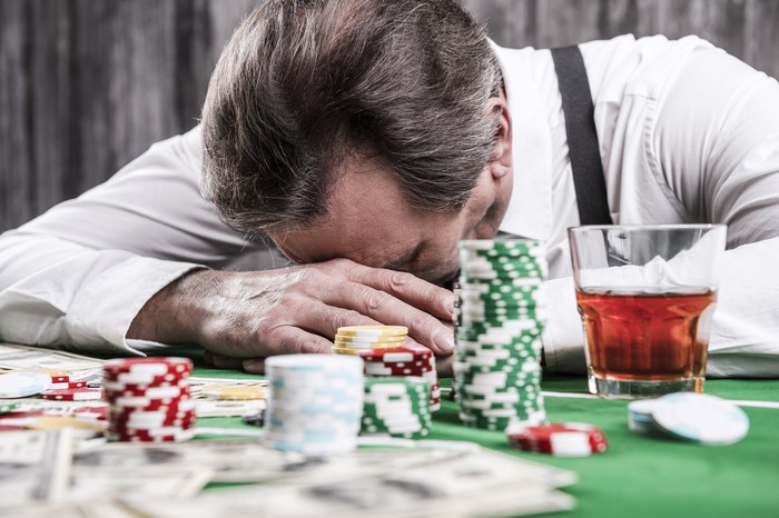A man with his head down on a poker table