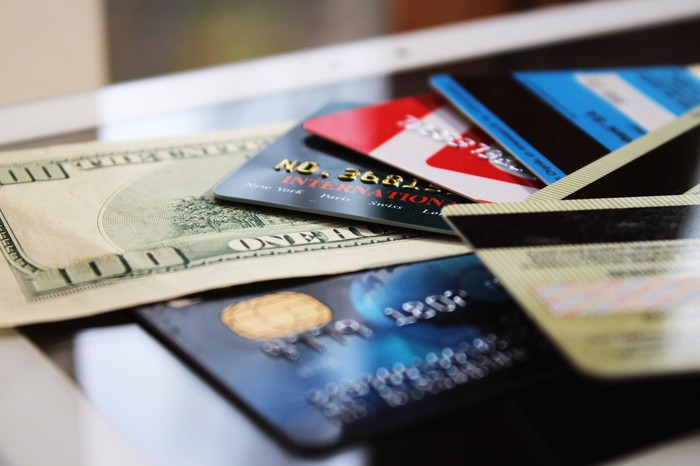 several credit cards spread out, with a hundred dollar bill between them
