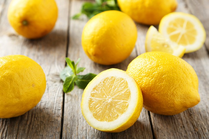 Lemons sitting on a wooden surface.