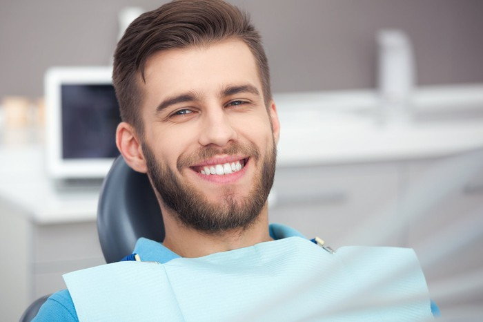 Man sitting in a dentist's chair, smiling.