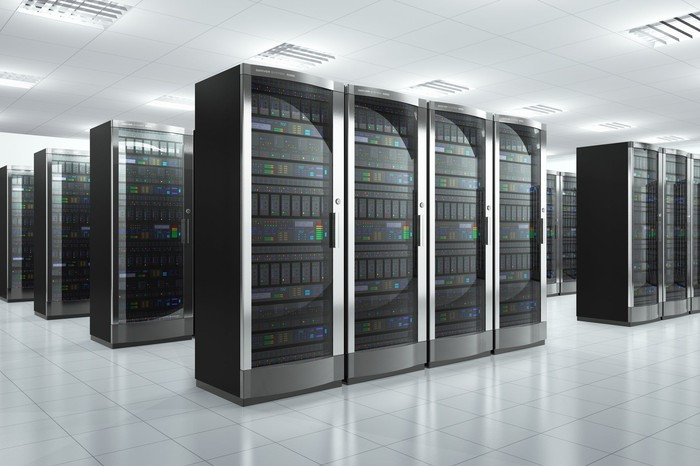 A brightly lit data center with many rows of server racks in silver and black.