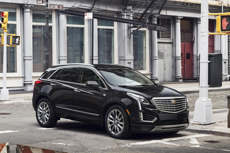 A black Cadillac XT5 crossover SUV on a city street.