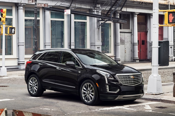 A black Cadillac XT5 crossover SUV on a city street.